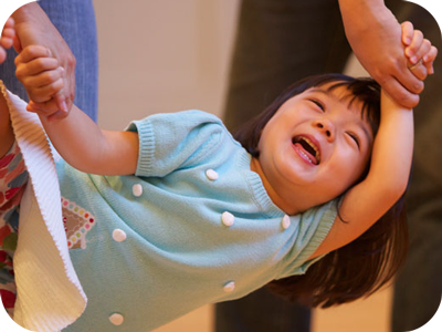 Little girl swinging from her mommy's hands in a Music Together class