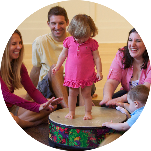 Little girl standing on drum in a Music Together class